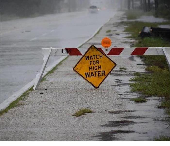 broken down high water sign in front of a road that has lots of water